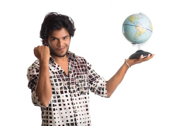 Jonge man met een wereldbol op een witte achtergrond.