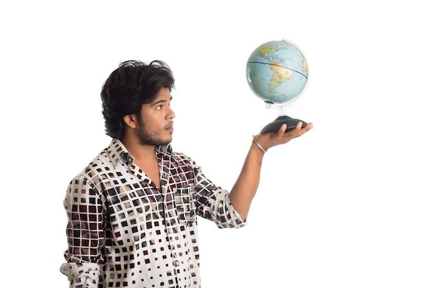 Jonge man met een wereldbol op wit