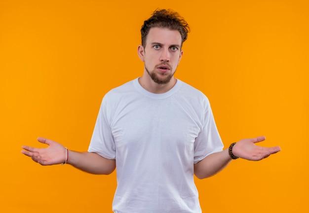 Jonge man met een wit t-shirt dat toont wat gebaar op geïsoleerde oranje muur