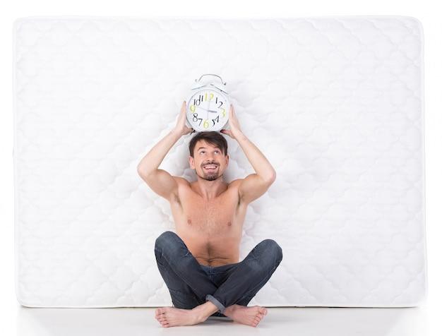 Jonge man met een witte matras en een klok.