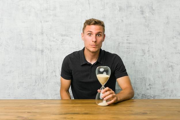 Jonge man met een zandloper op een tafel haalt schouders op en open ogen verward.