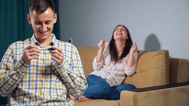 Jonge man met een zwangerschapstest kijkt terug op de gelukkige vrouw. geluk van het aanstaande ouderschap.