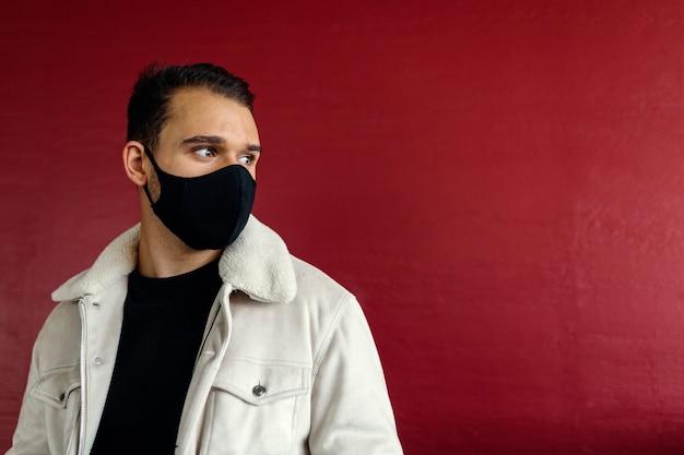 Jonge man met een zwart masker, wegkijkend, op een rode muur achtergrond in de straat. jeugd-, mode- en coronavirus-concept. afbeelding met copyspace.
