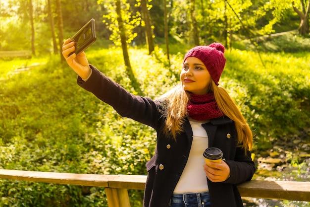 Jonge man met een zwarte jas, sjaal en rode wollen muts die geniet in een herfstpark, een selfie neemt met de mobiel, bij zonsondergang