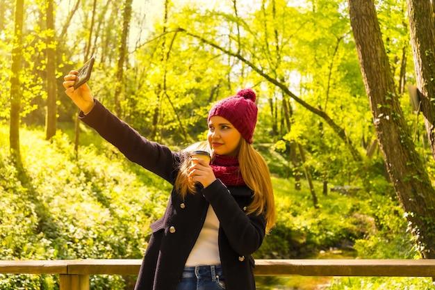 Jonge man met een zwarte jas, sjaal en rode wollen muts die geniet in een herfstpark en een selfie maakt met de mobiel