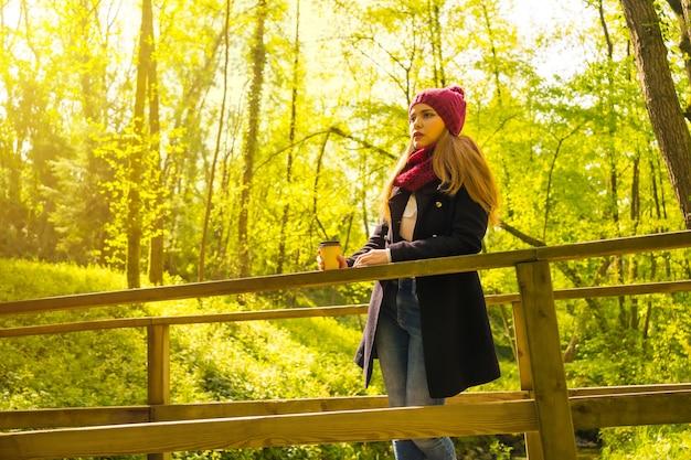 Jonge man met een zwarte jas, sjaal en rode wollen muts die geniet in een herfstpark