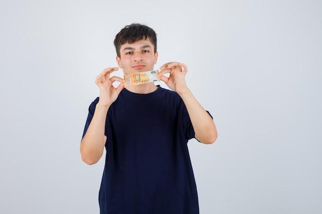 Jonge man met eurobiljet in zwart t-shirt en op zoek zelfverzekerd. vooraanzicht.