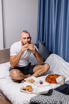Jonge man met fast food thuis in de slaapkamer op bed