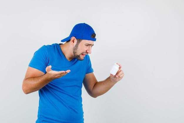 Jonge man met fles pillen in blauw t-shirt en pet en op zoek depressief