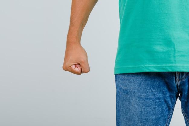 Jonge man met gebalde vuist in groen t-shirt, spijkerbroek en op zoek boos, vooraanzicht.