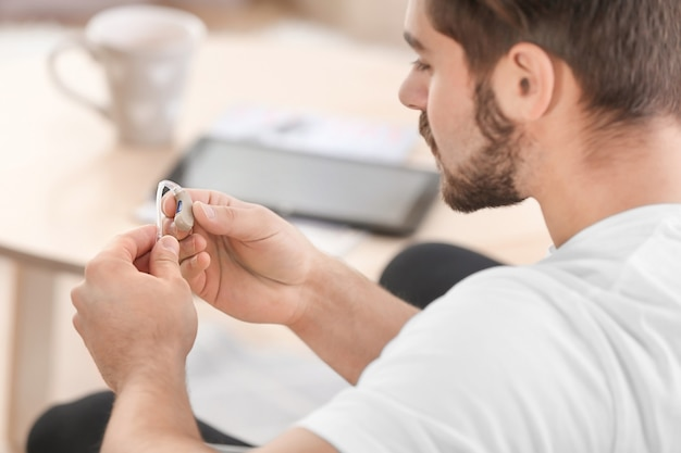Jonge man met gehoorapparaat binnenshuis