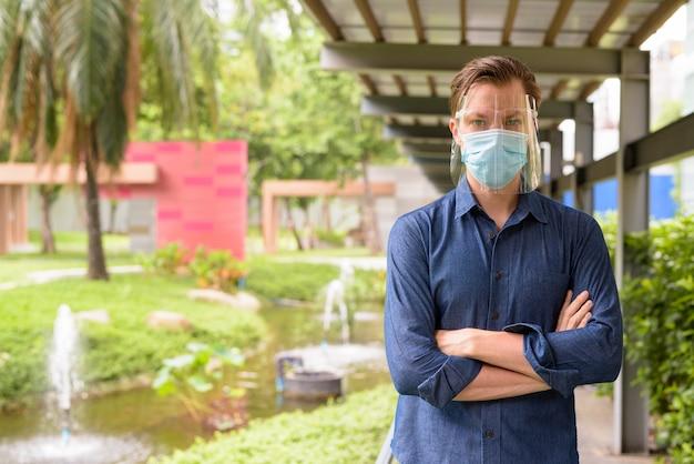 Jonge man met gekruiste armen dragen masker en gelaatsscherm voor bescherming tegen uitbraak van coronavirus in het park