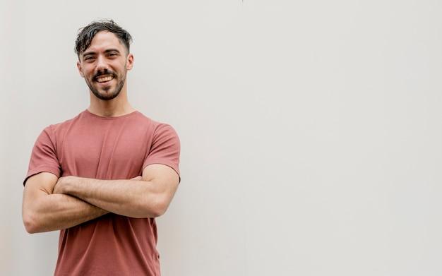 Jonge man met gekruiste armen en kopie-ruimte