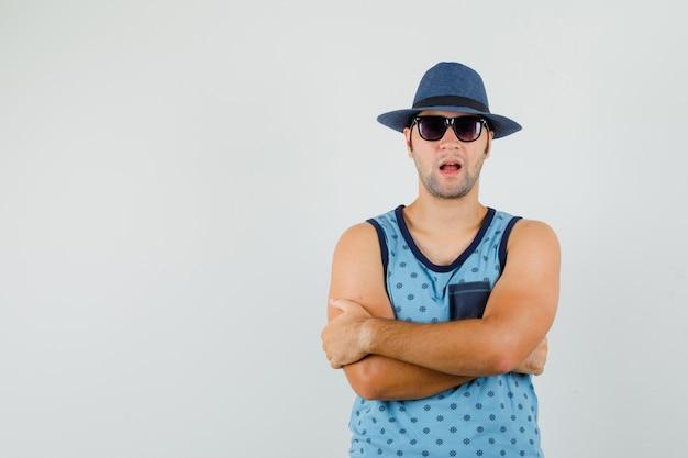 Jonge man met gekruiste armen in blauw hemd, hoed en op zoek zelfverzekerd, vooraanzicht.