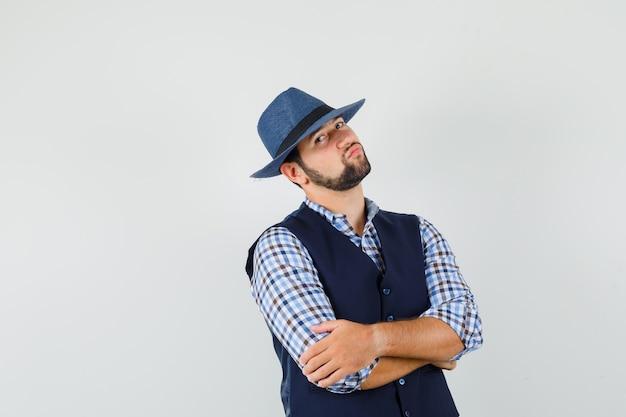 Jonge man met gekruiste armen in overhemd, vest, hoed en op zoek zelfverzekerd
