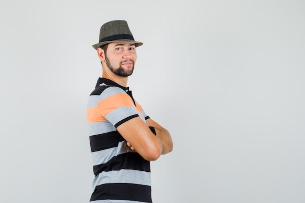 Jonge man met gekruiste armen in t-shirt, hoed en op zoek zelfverzekerd.