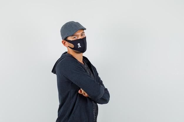 Jonge man met gekruiste armen in t-shirt, jas, pet, masker en op zoek zelfverzekerd.