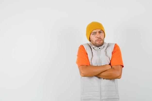 Jonge man met gekruiste armen in t-shirt, jasje, hoed en op zoek naar strikte