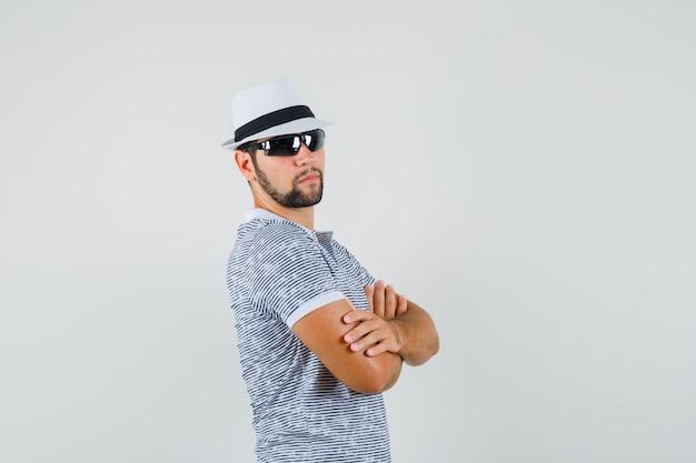 Jonge man met gekruiste armen in t-shirt, zonnebril en op zoek cool.