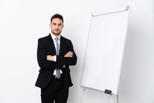 Jonge man met gekruiste armen terwijl het geven van een presentatie op wit bord