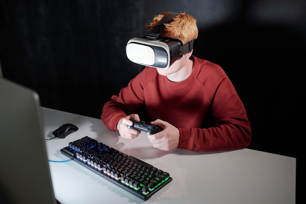 Jonge man met gemberhaar in vr-bril zit computerscherm tijdens het spelen van virtuele games 's nachts