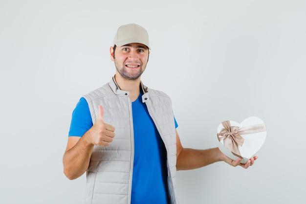 Jonge man met geschenkdoos, duim opdagen in t-shirt, jasje en op zoek vrolijk. vooraanzicht.