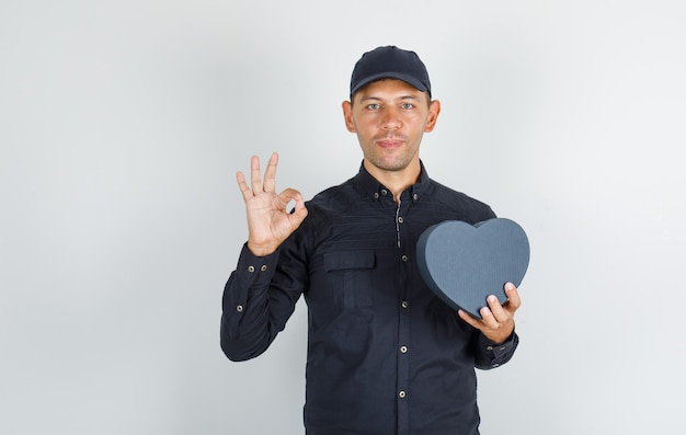 Jonge man met geschenkdoos en ok teken in zwart shirt met pet doen
