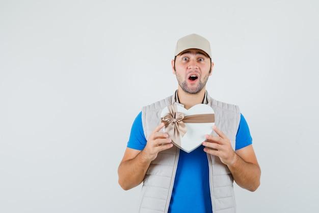 Jonge man met geschenkdoos in t-shirt, jas en op zoek gelukkig, vooraanzicht.