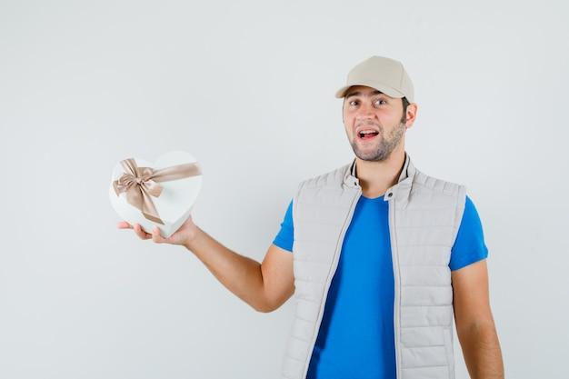 Jonge man met geschenkdoos in t-shirt, jasje en op zoek zelfverzekerd. vooraanzicht.