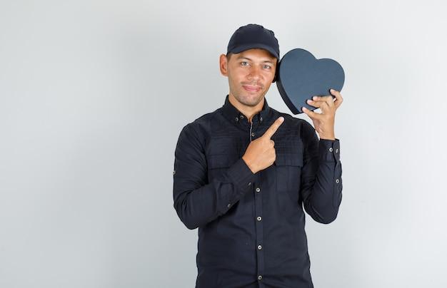Jonge man met geschenkdoos in zwart shirt met pet en op zoek vrolijk