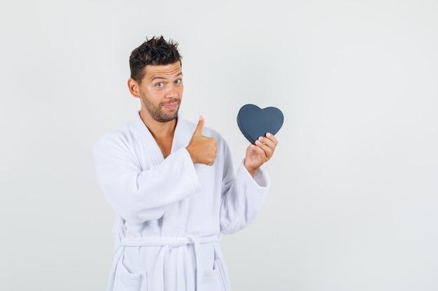 Jonge man met geschenkdoos met duim omhoog in witte badjas vooraanzicht.