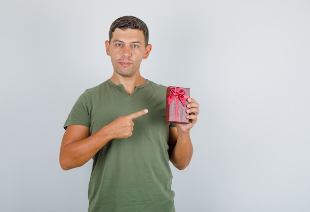 Jonge man met geschenkdoos met vinger in leger groen t-shirt vooraanzicht.