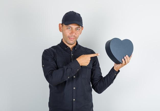 Jonge man met geschenkdoos met vinger in zwart shirt met pet