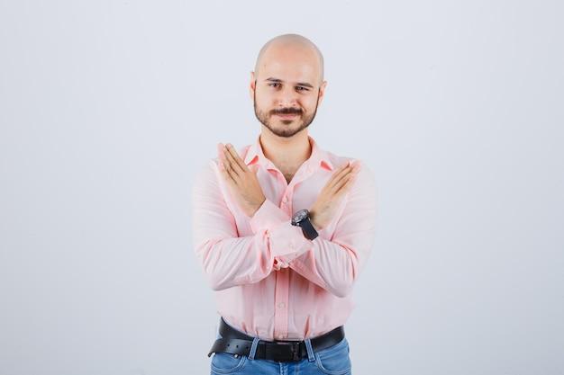 Jonge man met gesloten gebaar in roze shirt, spijkerbroek, vooraanzicht.