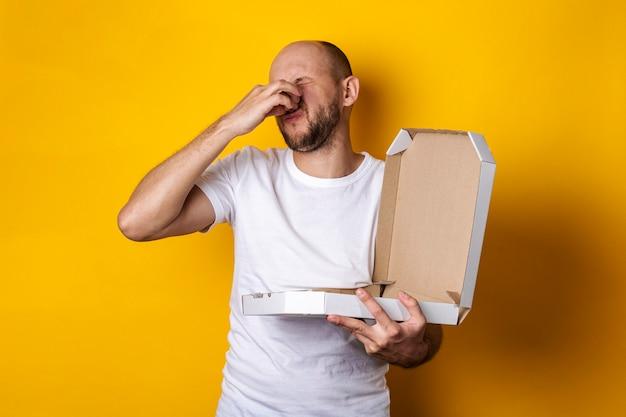 Jonge man met gesloten handneus houdt open pakket met pizza op gele ondergrond.