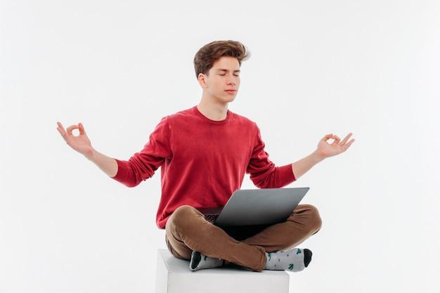 Jonge man met gesloten ogen zitten in de lotuspositie met laptop