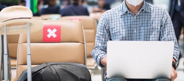 Jonge man met gezichtsmasker en met behulp van computer laptop in luchthaven, bescherming coronavirus-infectie, aziatische man reiziger zittend op een stoel. new normal, social distancing en digital nomad