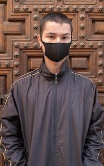 Jonge man met gezichtsmasker kijkend naar de camera tijdens de pandemie.