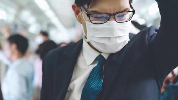 Jonge man met gezichtsmasker reist in overvolle metro