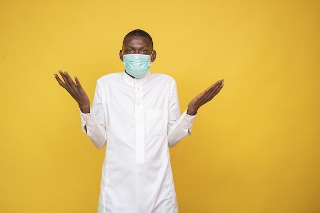 Jonge man met gezichtsmasker, schouderophalend - het nieuwe normale concept