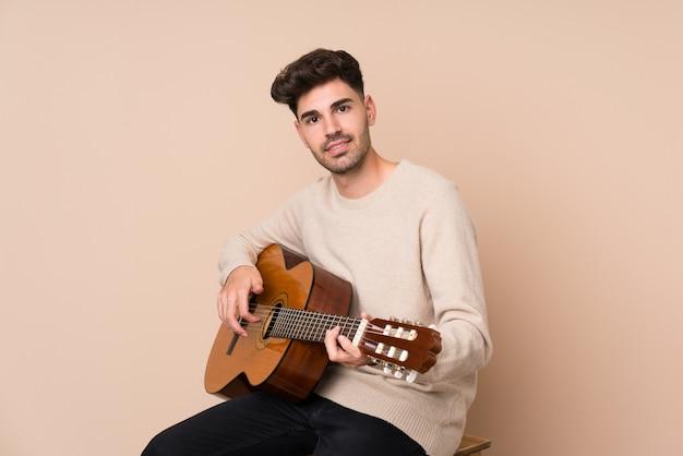 Jonge man met gitaar over geïsoleerde achtergrond