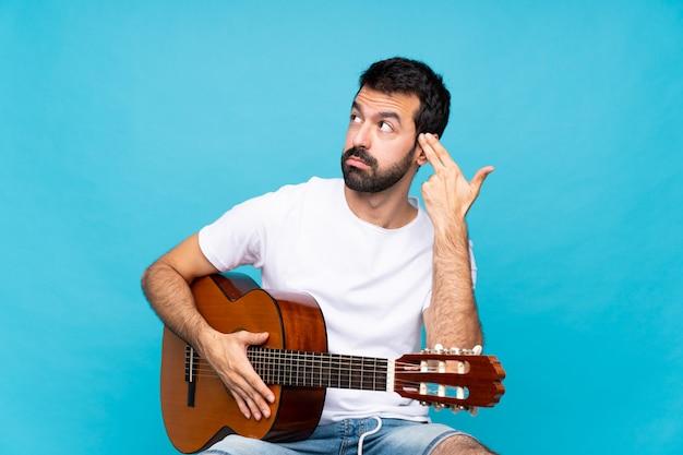 Jonge man met gitaar over geïsoleerde blauw met problemen die zelfmoordgebaar maken