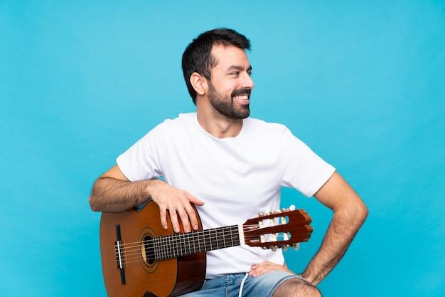 Jonge man met gitaar over geïsoleerde blauw poseren met armen op heup en glimlachen