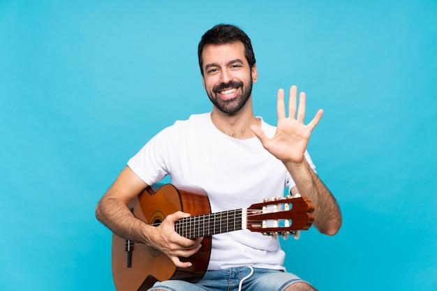 Jonge man met gitaar over geïsoleerde blauwe muur die vijf met vingers telt