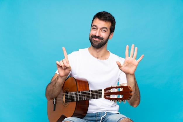 Jonge man met gitaar over geïsoleerde blauwe muur die zes met vingers telt