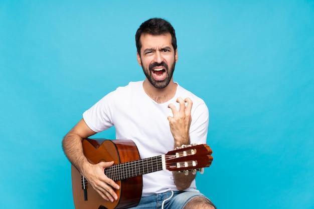 Jonge man met gitaar over geïsoleerde blauwe muur gefrustreerd door een slechte situatie