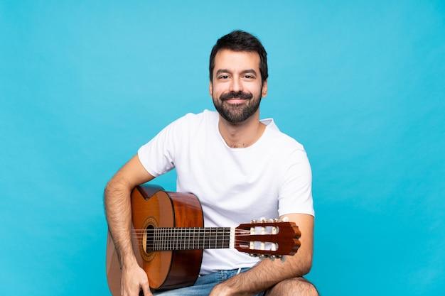 Jonge man met gitaar over geïsoleerde blauwe muur lachen