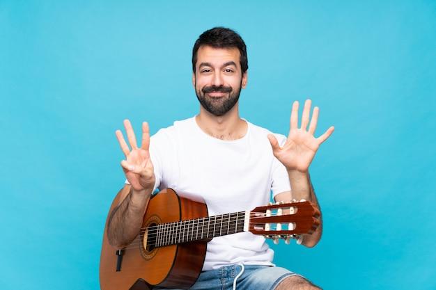 Jonge man met gitaar over geïsoleerde tellen acht met vingers