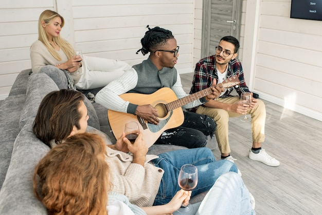 Jonge man met gitaar zingen voor zijn vrienden om hem heen op de bank zitten en met wijn thuis feest in de woonkamer