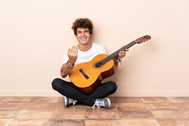Jonge man met gitaar zittend op de vloer
